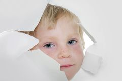 Child looking out from hole in paper Stock Images