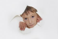 Child looking out from hole in paper. Cute boy looking out through hole in paper Royalty Free Stock Images