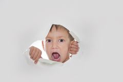 Child looking out from hole in paper. Young boy shouting loudly through hole in paper Royalty Free Stock Photography