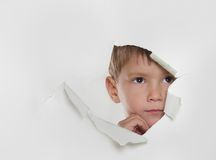 Child looking out from hole in paper Royalty Free Stock Photography