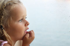 Child looking out of window. Little girl looking out of window covered with raindrops Royalty Free Stock Images