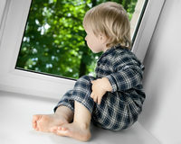 Child looking out window. Little blond boy sitting on windowsill looking out window Stock Photos