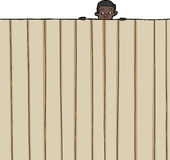 Child Looking Over Fence. Amazed male child looking over wooden fence Stock Photo