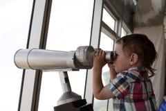 Child looking through pay binoculars Royalty Free Stock Photo