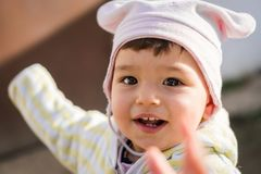 Child looking and pointing at camera smiling on a cold sunny day stock photography
