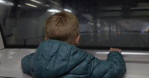 Child looking at railway from moving subway train. Back view of a little boy looking through the window of a moving subway train. On-coming train passing by in stock video