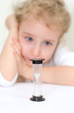 Child looking at sandglass. Little girl looking at sandglass Stock Photography