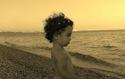 Child looking at the sea. A little child looking at the sea from the beach in sunset Royalty Free Stock Photography