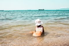 Child looking at the sea and ships stock photo