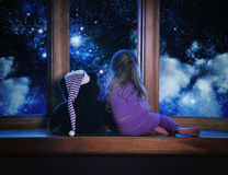 Child Looking at Space Dream in Window. A little child and her teddy bear are looking outside a window with space stars and clouds in the night for a astronomy royalty free stock photos