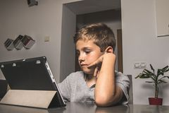 Child looking at a tablet. Middle-aged boy stock images