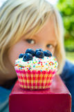 Child looking at tempting cupcake treat. Cupcake in focus. Child looking at colorful tempting cupcake treat. Cupcake is in focus stock photo