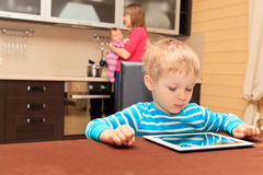 Child looking at touch pad while mother is cooking at home Stock Photo