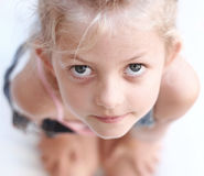 Child looking up. Girl looking up with hands on knees Royalty Free Stock Image