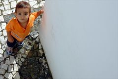 Child looking upward. Child holding wall and looking upward Royalty Free Stock Image