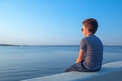 Child looking at water at sunset royalty free stock photo