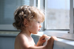 Child looking into window. Serious child attentively looks out of the window - shallow depth of field royalty free stock photo