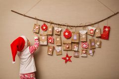 Child looks at the advent calendar. Baby girl in a Christmas hat and pajamas shows on first gift stock images