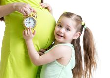 Child looks at alarm clock and pregnant woman Royalty Free Stock Image