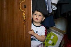 The child looks from behind the closet door. Kid hiding in wardrobe. The child looks from behind the closet door stock photo