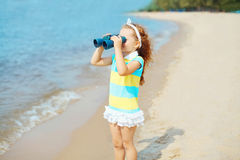 Child looks in binoculars on beach near sea. Little girl child looks in binoculars on beach near sea Royalty Free Stock Photo