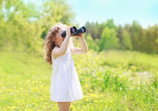 Child looks in binoculars outdoors in sunny summer Royalty Free Stock Photography