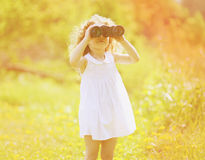 Child looks in binoculars. In sunny summer day Royalty Free Stock Photography