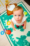 The child looks into the camera lens. Child playing with educational color pyramid toy Royalty Free Stock Photo