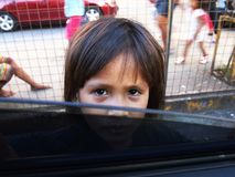 A child looks into a car window asking for some money. Royalty Free Stock Photo