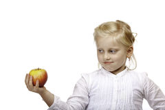 Child looks contemplative at healthy fruit (apple) Stock Image