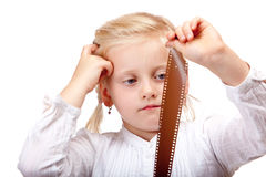 Child looks contemplative at old camera film Royalty Free Stock Photos