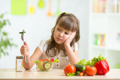 Child looks with disgust for food. Child girl looks with disgust for healthy food Royalty Free Stock Photo