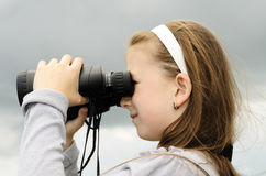 The child looks in the field-glass. The child the girl looks in the field-glass Royalty Free Stock Photo