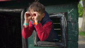 The child looks into his hands imitates binoculars, looks out of the window. Portrait child looks into hands imitates binoculars, looks out of a window stock video footage