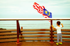A child looks at Malaysian flag Stock Images