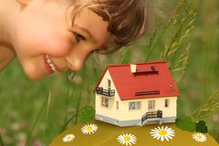 Child looks on model of house outdoor Royalty Free Stock Photo