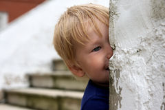 Child looks out. From the wall and smiles Stock Photography