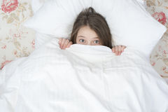 Child looks out from under the blanket. Stock Photos