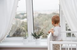 A child looks out the window. From the bed Stock Photography