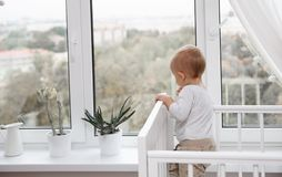 A child looks out the window. From the bed Royalty Free Stock Photography