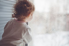 A child looks out the window. Royalty Free Stock Photos