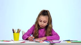 Child looks at the pictures and for a long time chooses which color to decorate. White background. Slow motion stock video