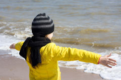 Child looks at the sea, arms outstretched. Stock Photo