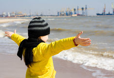 Child looks at the sea, arms outstretched. Stock Photos