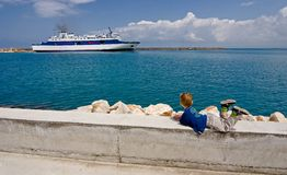 Child looks on the ship. In the port Stock Photography