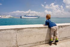Child looks on the ship. In the port Royalty Free Stock Image
