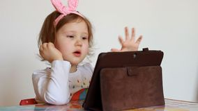 Child looks on the tablet screen and plays downloaded application. A little cute girl is sitting at a table, looking tv. Cartoon and playing the game on a stock video footage