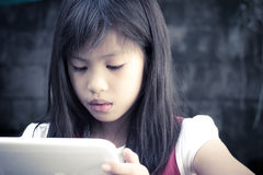 Child looks to the tablet computer Royalty Free Stock Photo