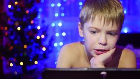 The child looks to the tablet lying on bed.On the background lights garlands stock footage