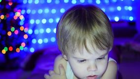 The child looks to the tablet lying on bed. In the background, lights and garlands of Christmas fir stock video